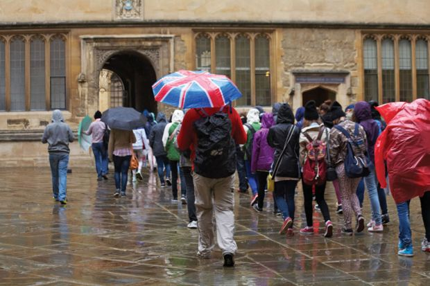 Tourists in rain outside Bodleian Library, University of Oxford