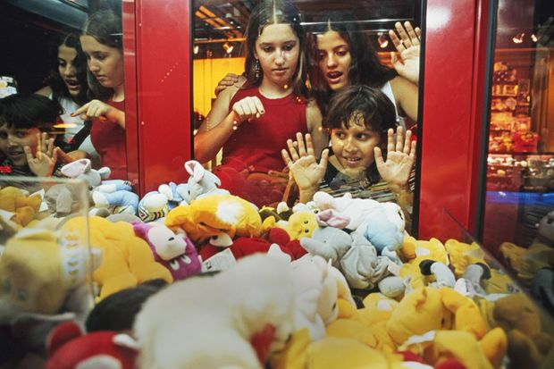 Children look at soft toys