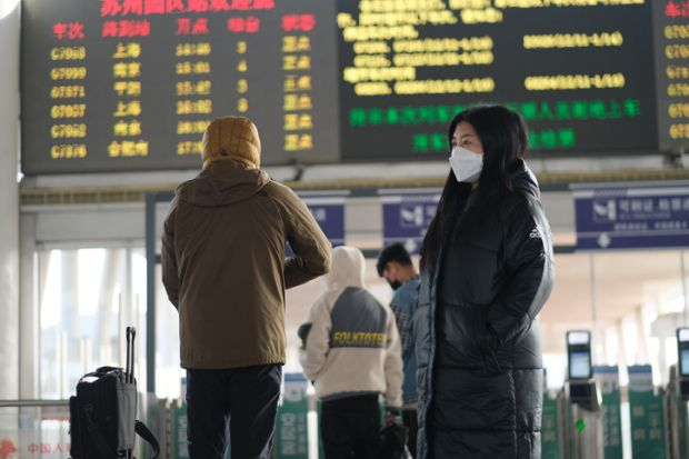 A traveller in a face mask at a railway station in Suzhou, China, illustrating the downturn in Chinese international students post-Covid