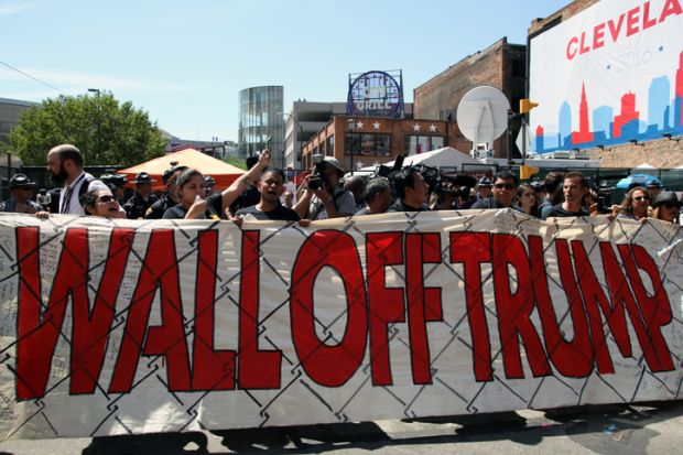 Cleveland, Ohio, USA - July 20, 2016: Participants in the 'Wall Off Trump' immigration march and rally demonstrate outside the Quicken Loans Arena, site of the Republican National Convention, on its third day.