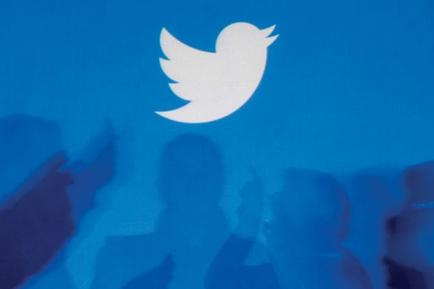 Twitter logo above silhouettes of people in discussion