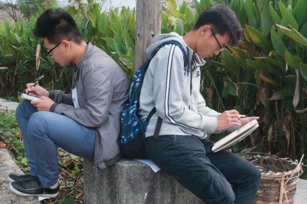Two male art students sketching back-to-back, Hongcun village, Anhui, China