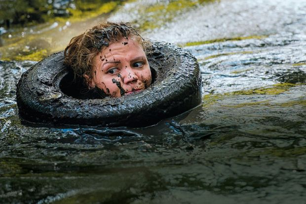 Woman in tyre in muddy river