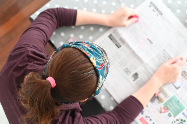 Unemployed woman searching for job in local newspaper