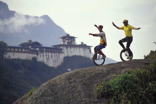 Two unicyclists on a hill