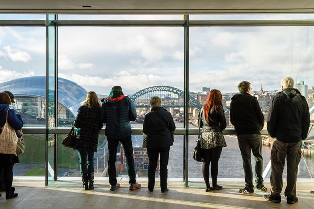 People looking out the window of the Baltic at the city view of Newcastle upon Tyne