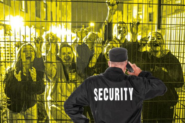 Security guard in front of fence with crowd smiling people behind
