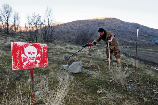 Person walks in a minefield trying to deactivate the devices on the outskirts of the Kurdish town of Halabja, Iraq as a metaphor for 'Tech without humanities leads to problems'