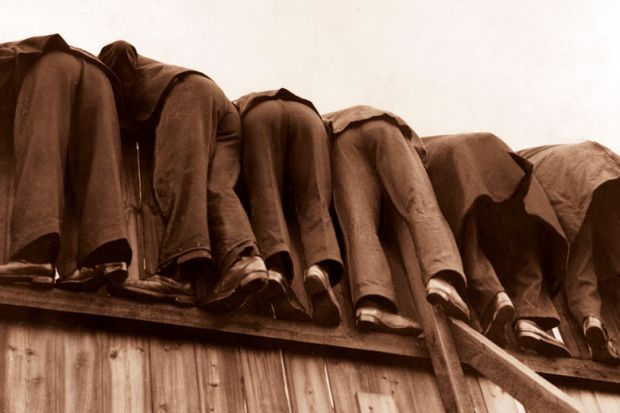 row of men bent over fence