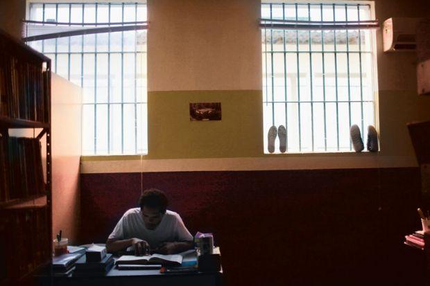 prisoner at desk with book