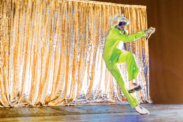 Person performing on stage, with neon green suit and blonde wig relating to scholars performing in their own online space, and being free to express themselves