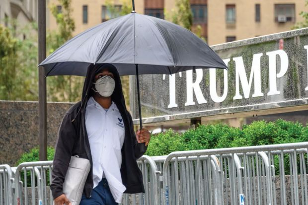 A person wears a protective face mask outside Trump International Hotel & Tower New York