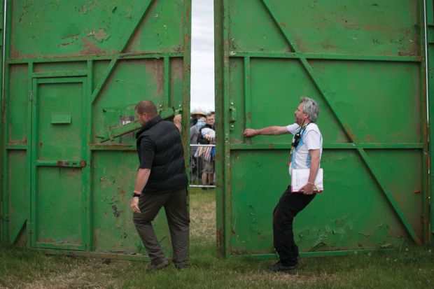 Stewards open the gates to ticket holders at a festival