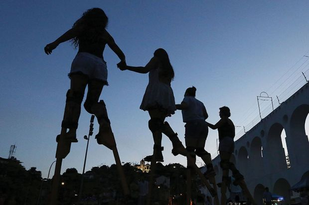 People practice walking on stilts during a stilt walking workshop as part of pre-Carnival festivities