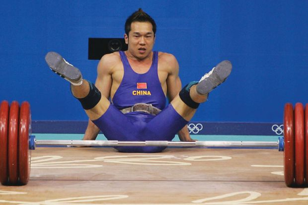 Weightlifter representing China drops the weight and falls on floor as a metaphor that Chinese excellence drive 'may make universities weaker'