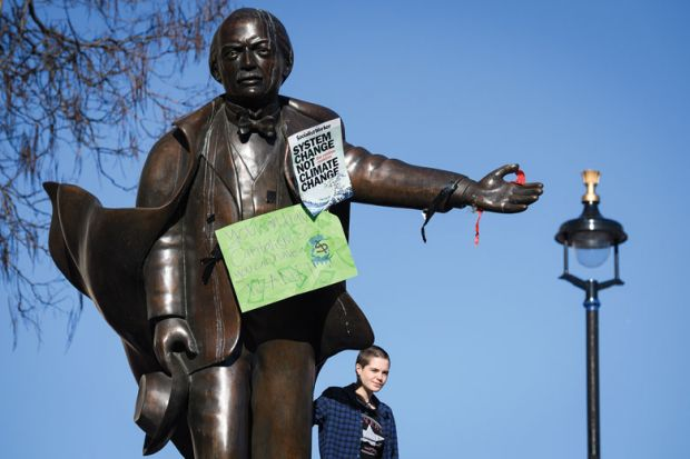 A student stands on the plinth of a statue of former Prime Minister David Lloyd George with climate change posters on the statue as a metaphor for picking fights with students 'deflection strategy' for ministers
