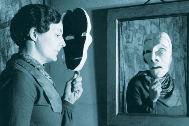 woman looking in mirror holding a mask as a metaphor for Academic conclusions differ wildly even on same data, study finds