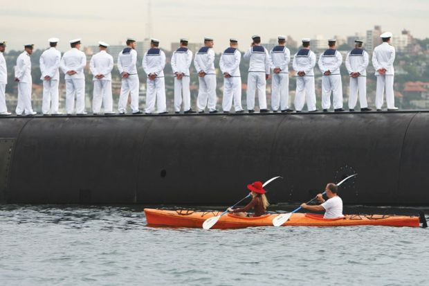 Sailors stand in line with a boat going behind them as a metaphor for Defence research 'antidote' to Covid's lost billions: thinktank