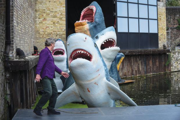 Person in front of a display of a group of full-scale replica sharks as a metaphor for Predatory journals jeopardise PhDs
