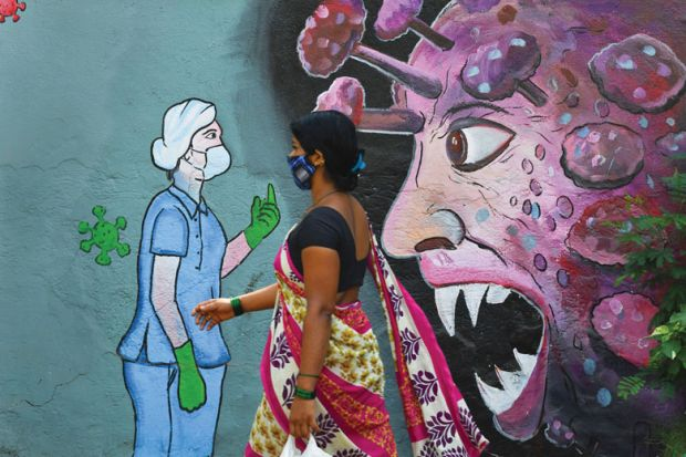 A pedestrian walks past a wall mural depicting a frontline medical staff stopping the Covid-19 as a metaphor for Research on viruses is  essential but can never be risk- free