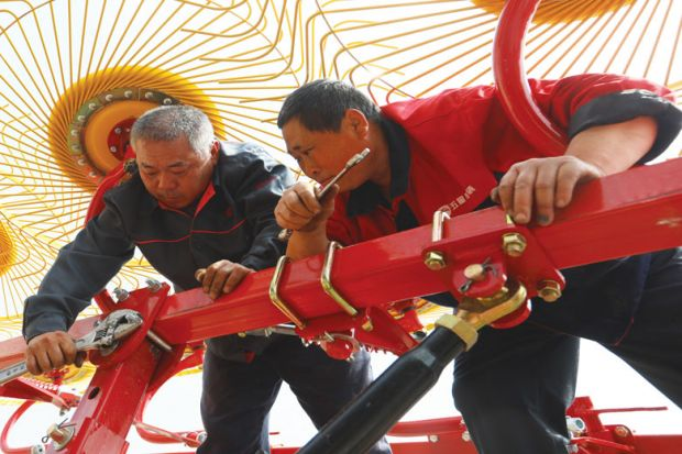 Equipment technicians repair a wheel rake in a field in China as a metaphor for overseas students fear losing degrees as China borders stay shut