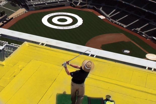 Player hits golf ball off a roof attempting to land the ball on a balls-eye planted in a field as a metaphor for Now is the time to take action on the UK's R&D spending target