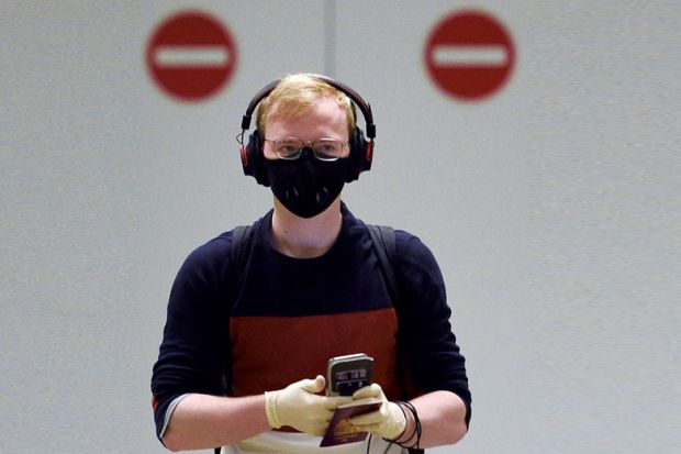 A passenger wearing PPE with two no entry signs behind him.