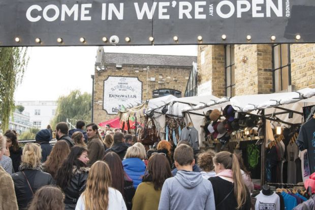 """crowds passing under an entrance sign reading """" Come in We're (very) Open."""