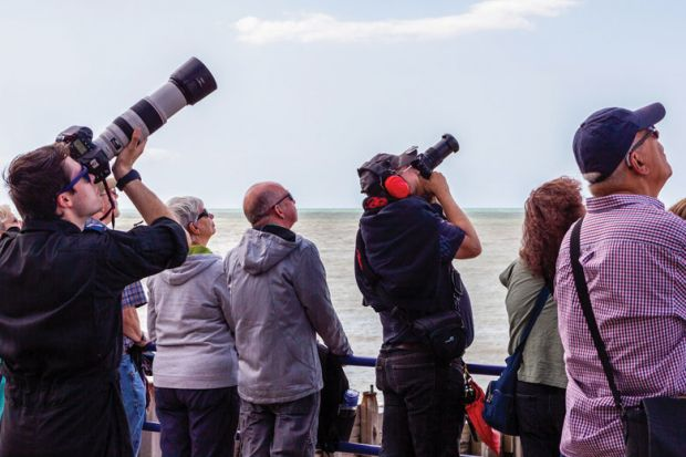Group of photographers look to the sky waiting ready to take pictures.