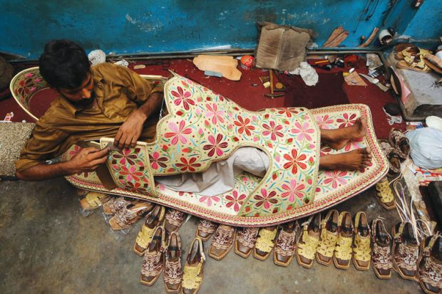 A Pakistani shoe maker, Hameed, sits inside a giant shoe at his shop in Lahore.