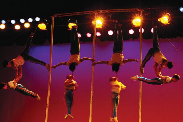 Acrobats linking arms in the air