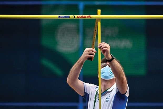 The high jump bar height is adjusted and measured by an official to illustrate English universities await clarity onimpact of GCSE entry bar