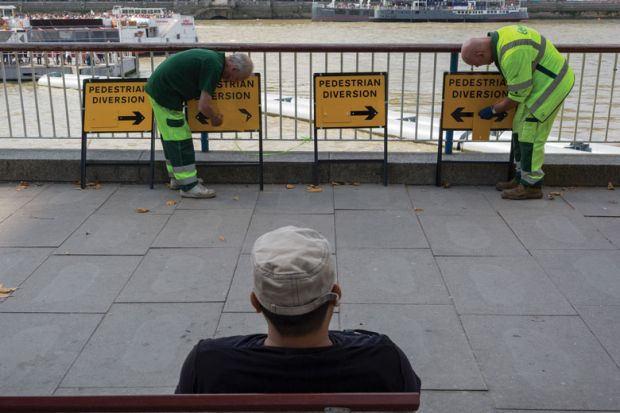 Workmen adjusting diversion arrows signs to illustrate 'Mixed messages' on face coverings on campus 'harms compliance'