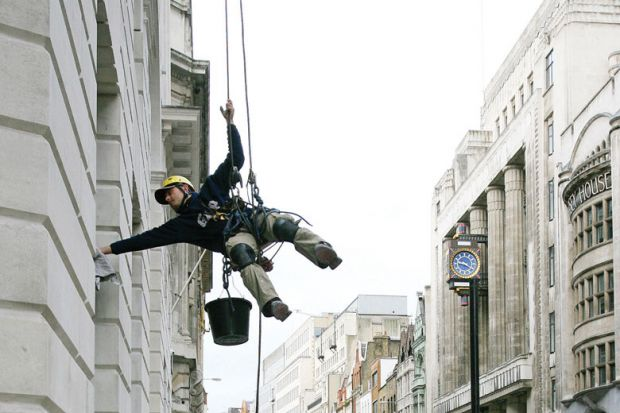 Image of a man suspended from ropes cleans an office in central London as metaphor for that universities in London will be tipped into deficit or pushed further into the red