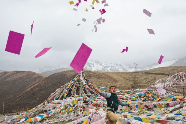 A Tibetan man throws prayers in the air at a high altitude as a metaphor for leading Chinese universities axe publication condition for PhDs