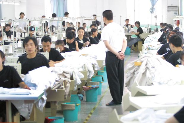 China, sweatshop manager standing watching workers