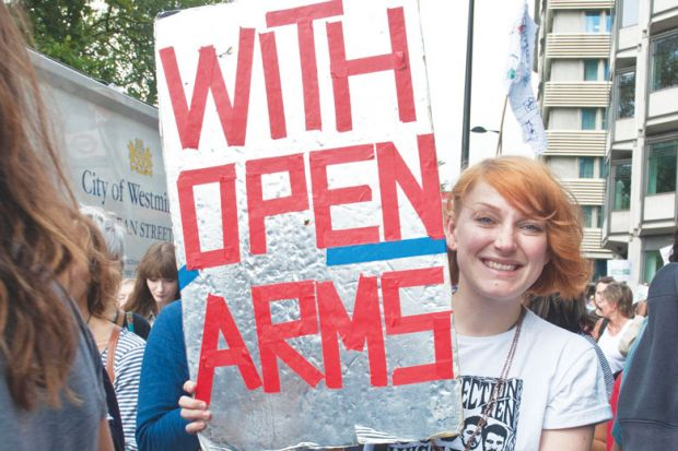 Person in a refugee demonstration London UK holding a banner reading 'With Open Arms'