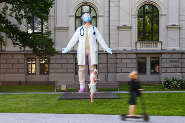 """A woman on a scooter drives past a 6 meters high statue of a female doctor by Latvian artist Aigars Bikse called """"Medics to the World"""" as a metaphor for 'Dramatic' variation in universities' occupational health expenditure"""
