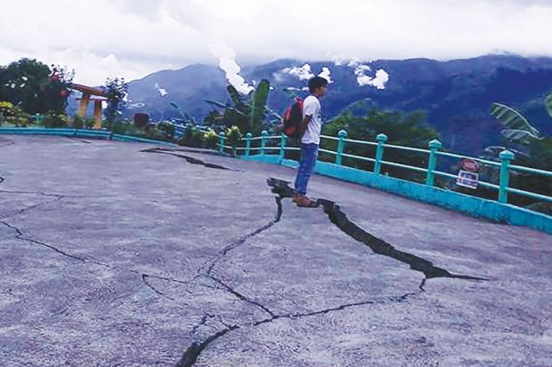 Person stands next to cracks in the ground at a park in Leyte province, central Philippines as a metaphor for the pan-regional university risks being split by the same tensions