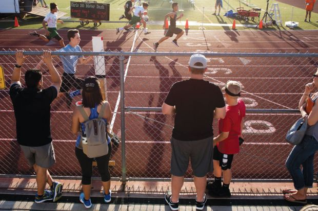 People watch from behind the fence as the athletes cross the finish line as a metaphor for the wealth gap widening as US elite report record enrolments