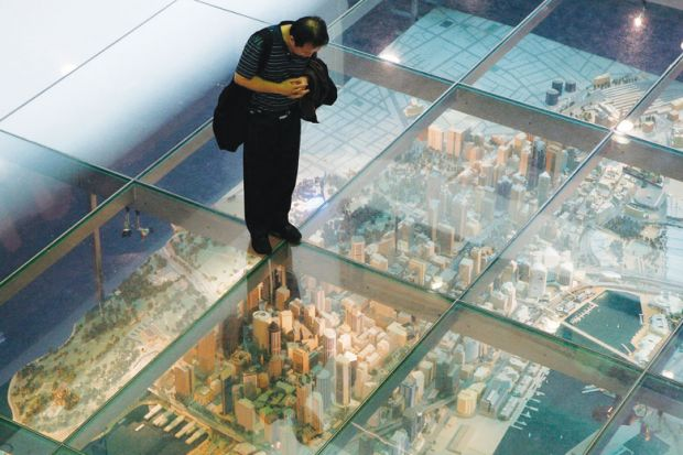 Person looks at a model of Sydney's central business district in central Sydney under a glass floor as a metaphor for China moves to halt universities' eastern branch campus rush