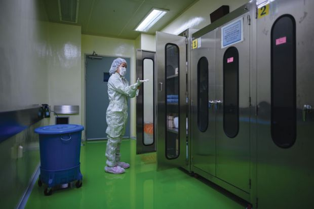 A lady putting on protective clothing required to enter a testing lab