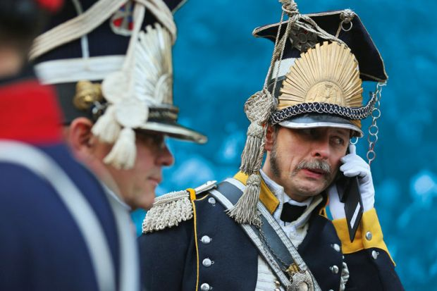 An actor in the role of a soldier in the 7th Polish Lancer Regiment talks on a mobile phone upon his arrival for the opening ceremony to commemorate the 200th anniversary of The Battle of Nations