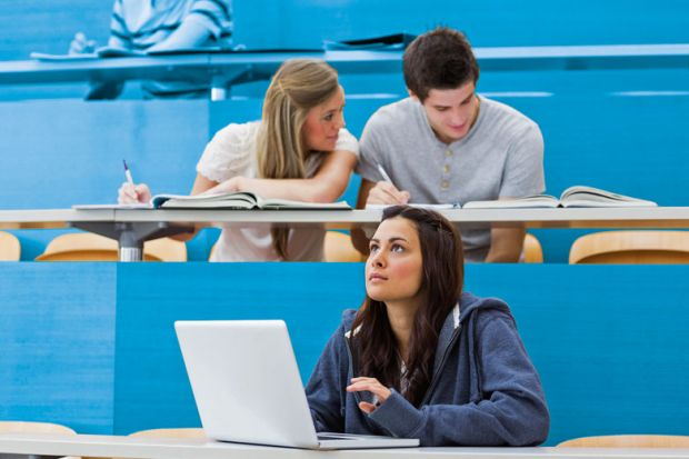 Students sitting in lecture with girl thinking at laptop