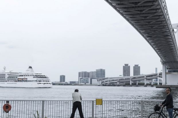 A man observes a ship passing under the Rainbow Bridge in Tokyo, Japan as a metaphor for Japan 'will  miss the boat'  if it doesn't  go global