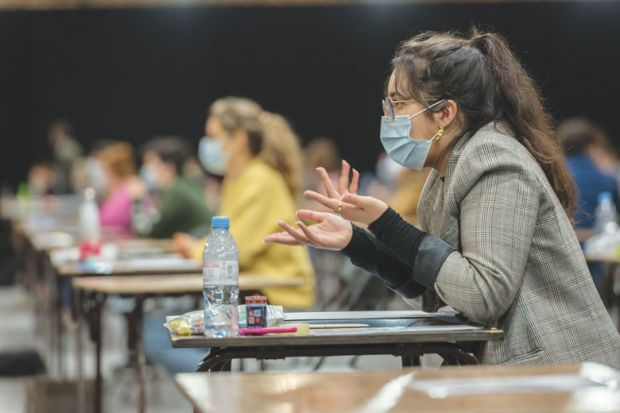 Student wearing mask at the desk in an exam hall as a metaphor for a test of resilience