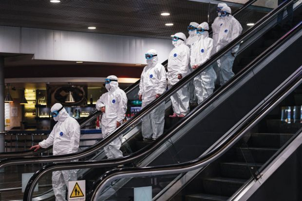 Medical staff wearing protective suits ride down an escalator for Leadership turnover rate could double