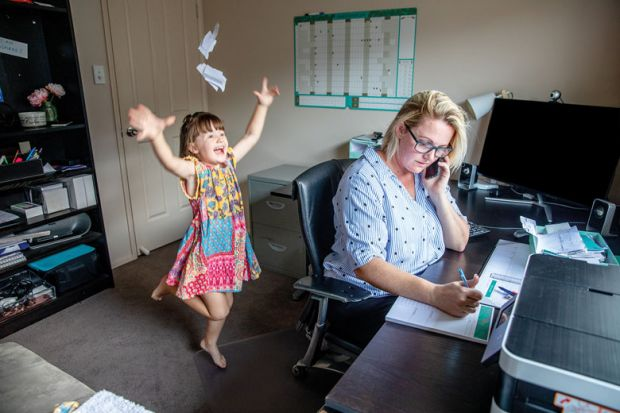 Mother attempts to work from home on the computer and phone whilst her daughter copies her, makes a mess and throws the laundry around. for University staff less happy and more anxious than UK average