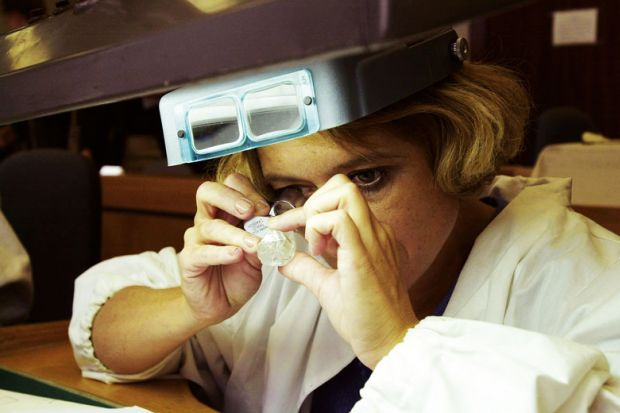 A sorter inspects a 143-carat Russian diamond for France to back not-for-profit diamond journals