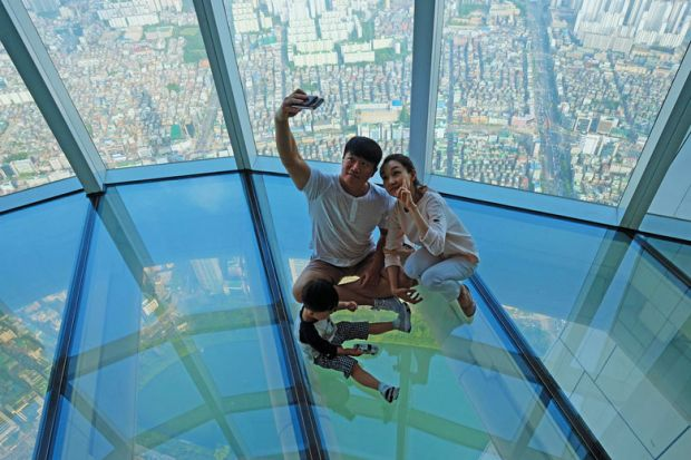 A Korean family taking selfie photo at the glass floor observatory of Lotte World Tower  for Top Korean universities more 'glass floor' than 'social ladder'